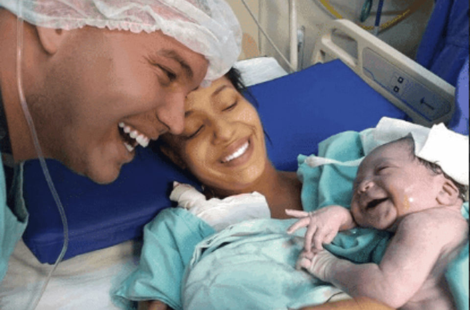 A newborn baby girl smiles as she recognizes the voice of her father