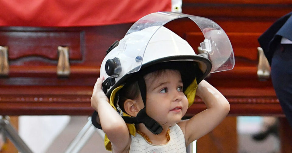 20-month-old girl wears Australian firefighter dad's helmet and refuses to leave his side at funeral